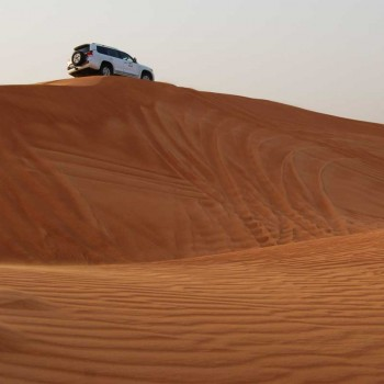 Two cars on a desert dune near Dubai