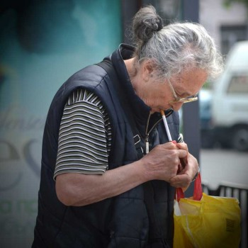An old woman lights her cigarette in Sofia, Bulgaria