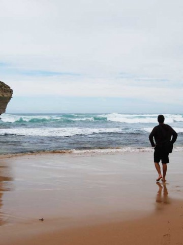 A man who is traveling alone is watching the ocean at Great Ocean Road, Australia.