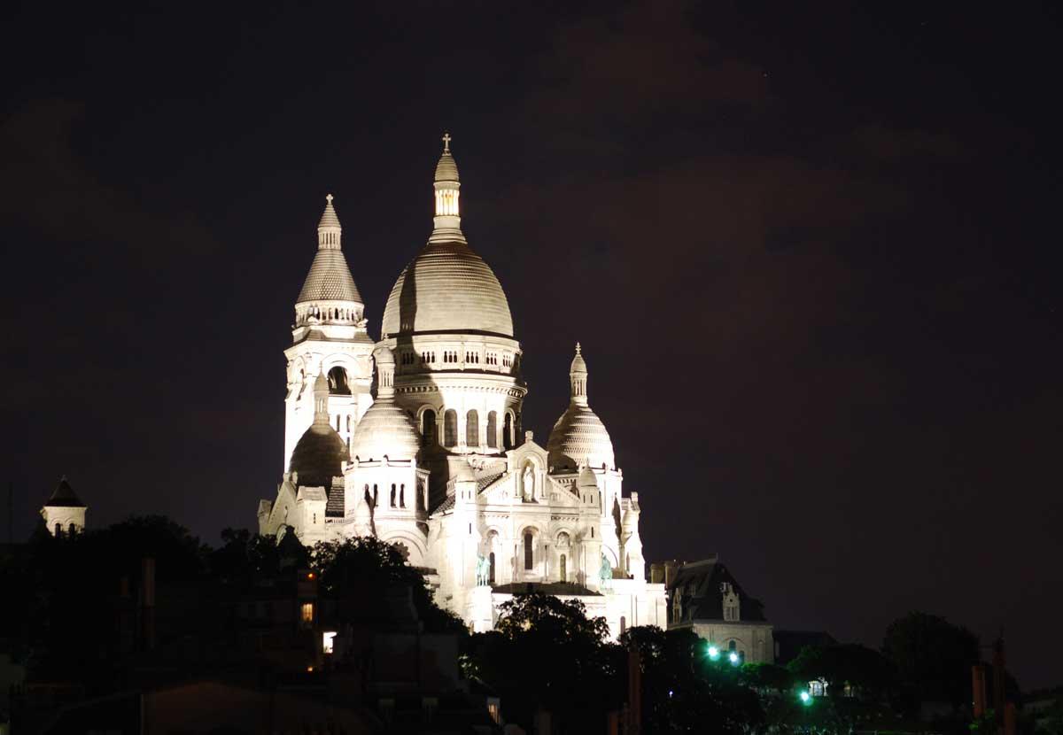 Die Basilika Sacré-Coeur de Montmartre in Paris bei Nacht angeleuchtet