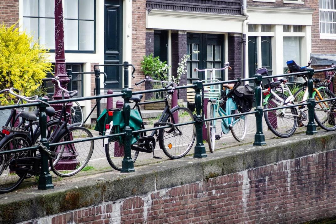 In Amsterdam gibt es mehr Fahrräder als Einwohner. Zu sehen sind sie überall - hier festgekettet an einem Grachtengeländer.
