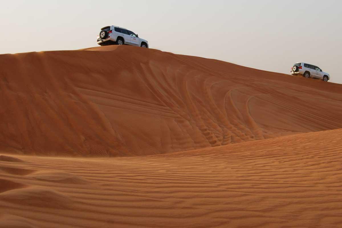 Two cars on a desert dune near Dubai