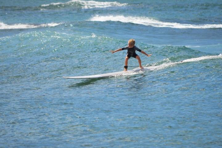 Ein kleiner Junge surft in Haleiwa, Oahu