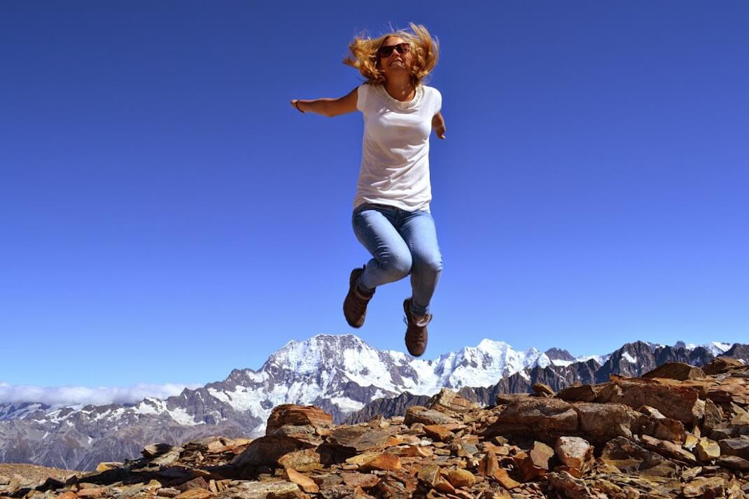 Julia jumping in New Zealand mountain scenery