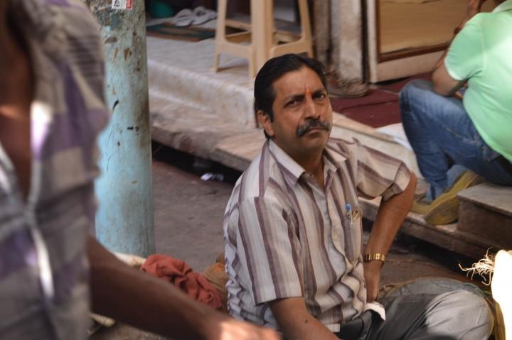 Indien in Bildern Ein Mann sitzt in der Alststadt von Delhi vor seinem Laden