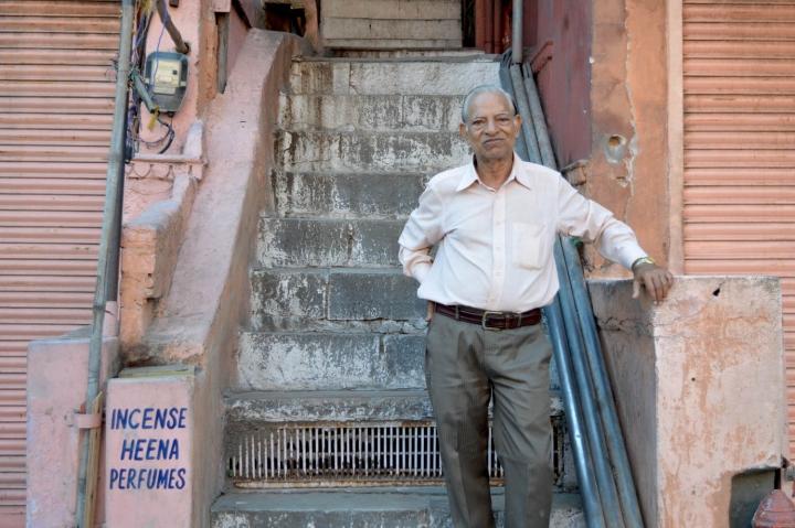 Indien in Bildern Ein Mann steht vor seinem Laden in Jaipur gegenüber dem Palast der Winde