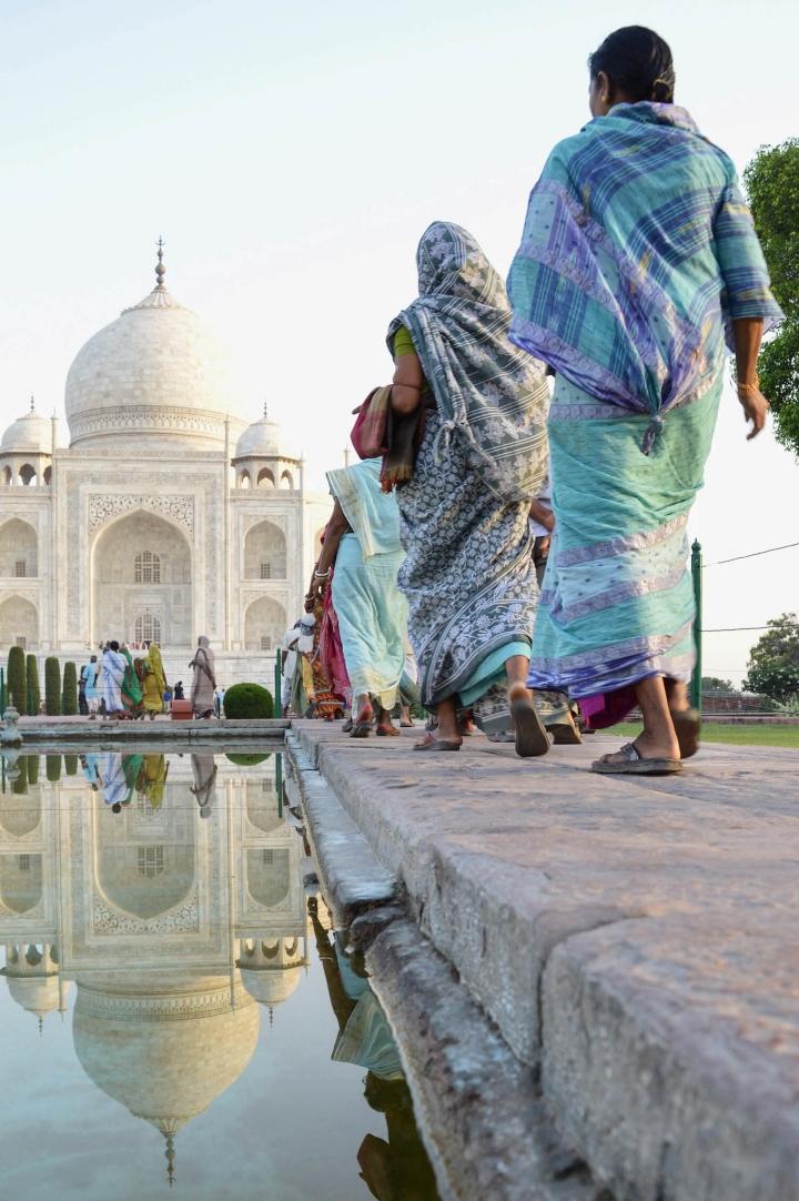 Indien in Bildern Eine Reihe von Frauen in Saris läuft auf das Taj Mahal zu