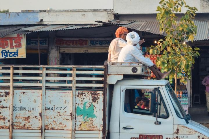 Indien in Bildern Zwei Männer sitzen auf dem Dach eines LKW