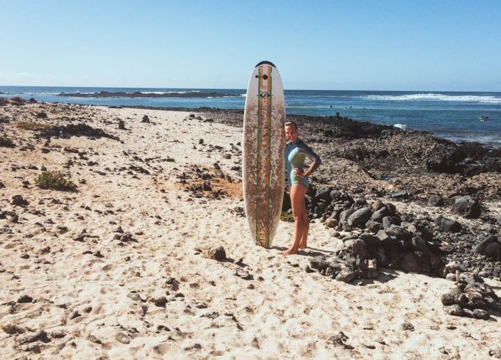 Surfen auf Fuerteventura Planet Surfcamps Anna mit Surfbrett am Strand von Punta Blanca
