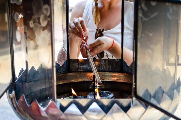 Im chinesischen Tempel in Bangkok zünden die Besucher Räucherstäbchen an