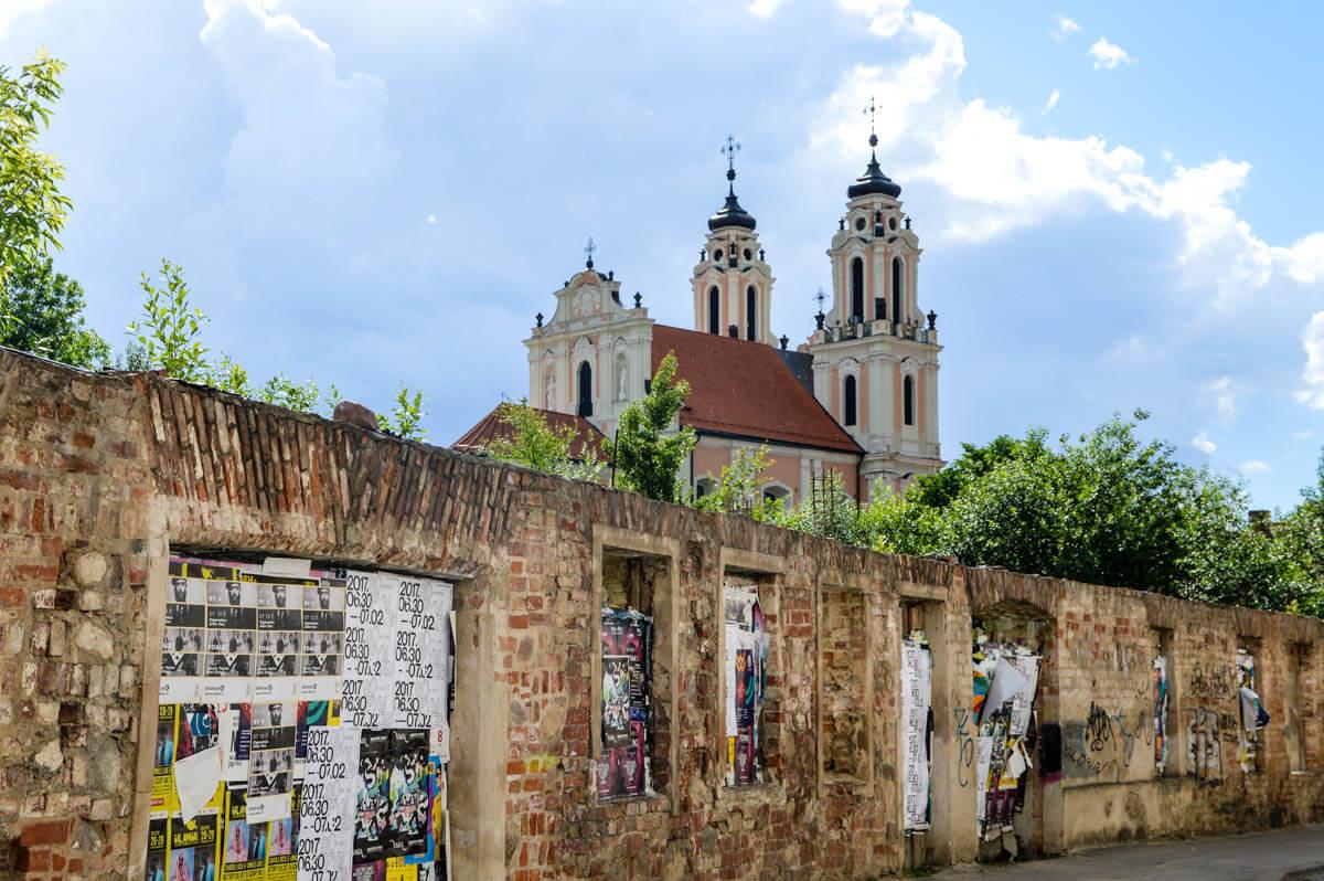 Vilnius Tipps für den Städtetrip: Heruntergekommene Mauer mit prunkvoller Kirche im Hintergrund