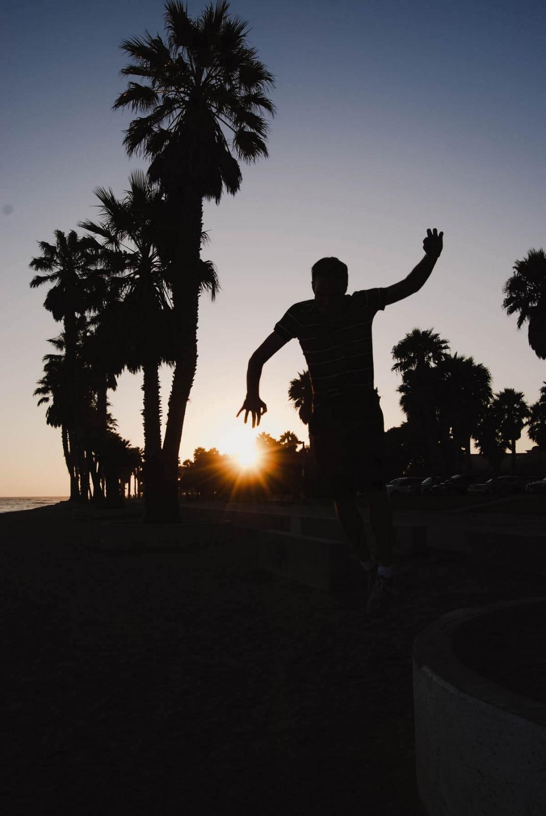 Kalifornien Silhouette von Palmen und Person im Sonnenuntergang