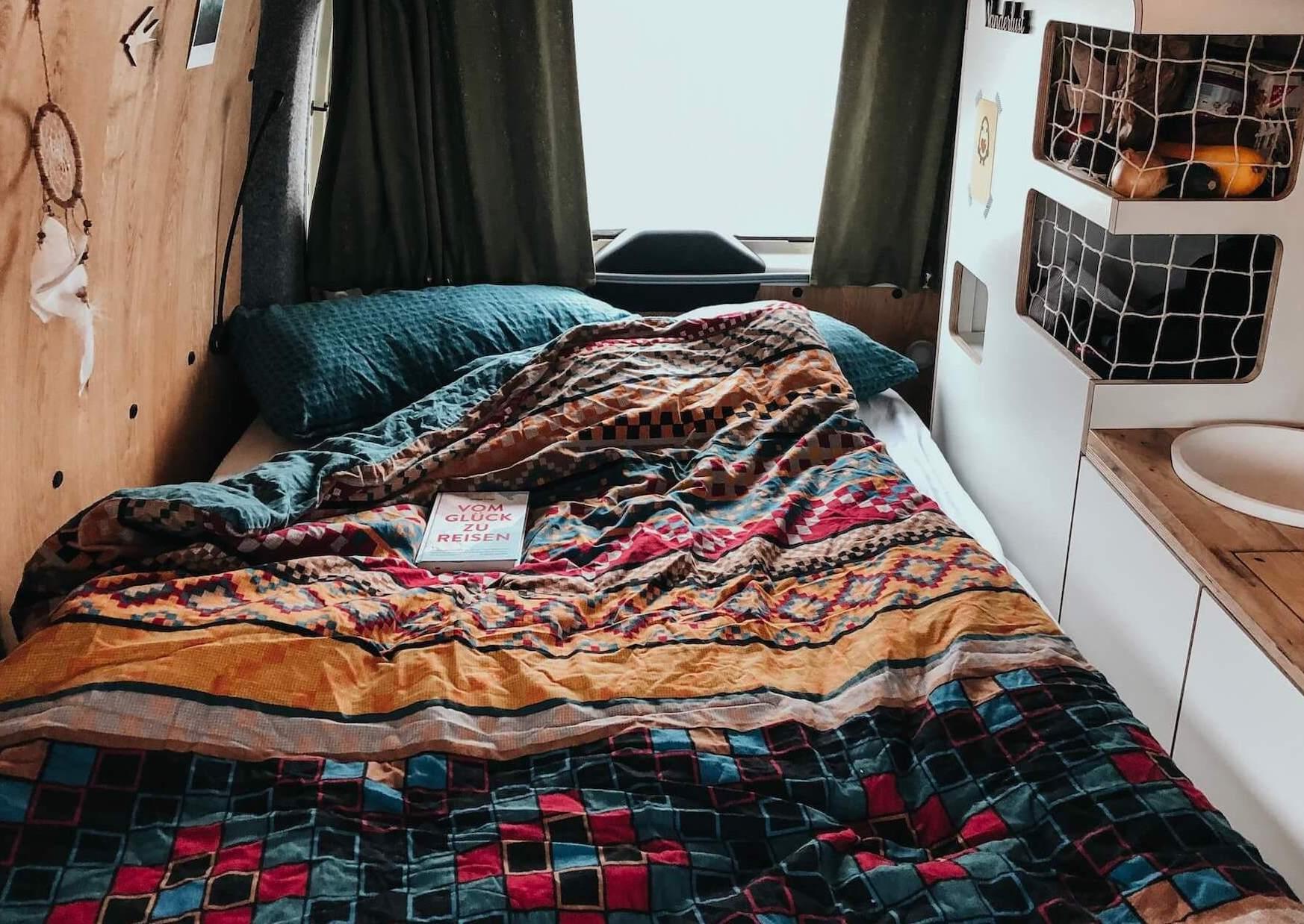 Vanlife im Camper von Vantopia Roadtrip ausgeklapptes Bett mit Bettdecke