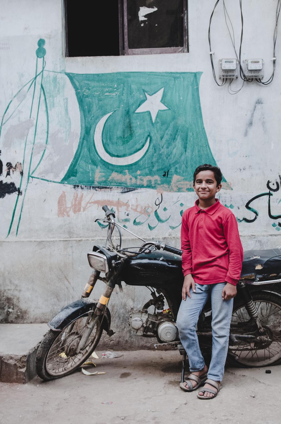 Ein Junge mit einem Mofa in Karatschi Pakistan